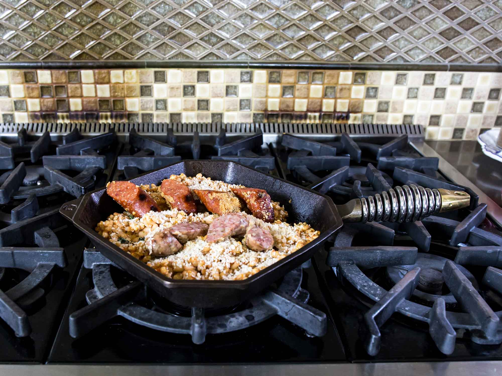 "10"" cast iron grill pan with sausage on stove"